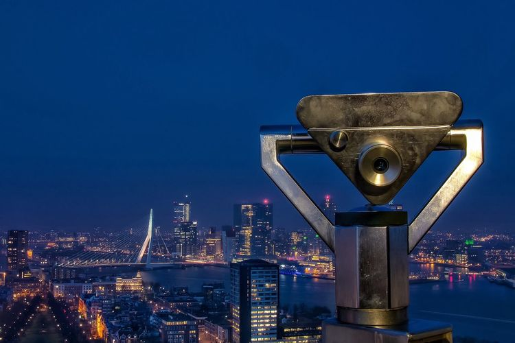 Coin-Operated Binocular By Illuminated Cityscape Against Sky At Dusk