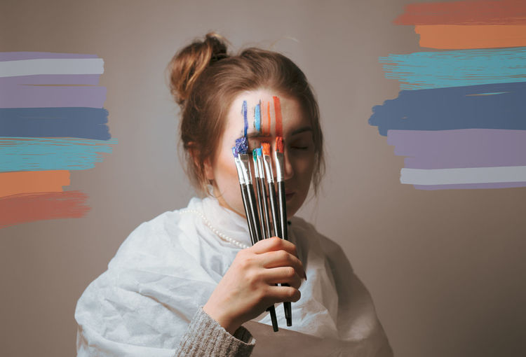 Young woman painting face against wall
