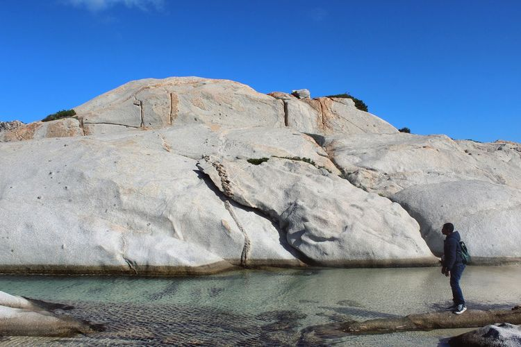 Man standing by rock formation at beach in la maddalena