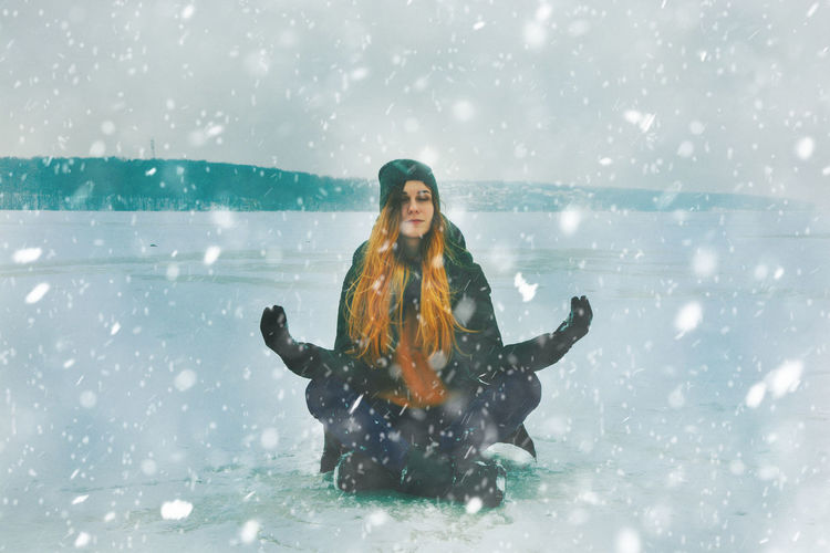 Full length of young woman enjoying snowfall while sitting on snowfield