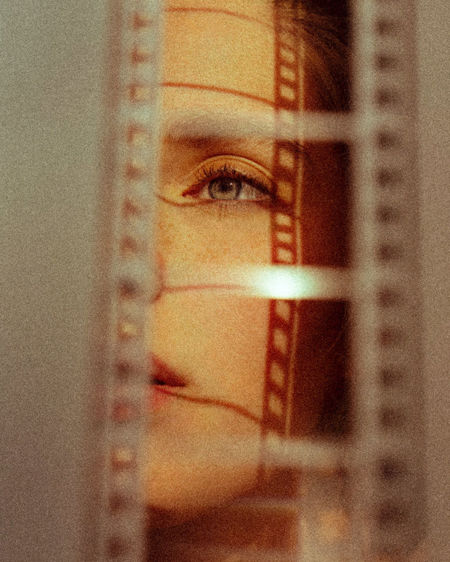 Close-up of woman looking through glass window