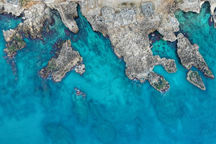 Aerial view of rock formations by sea