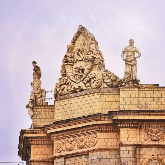 Building With Stone Statues Against Sky