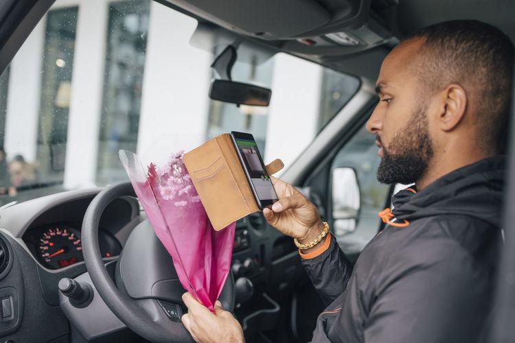 Man holding camera in car