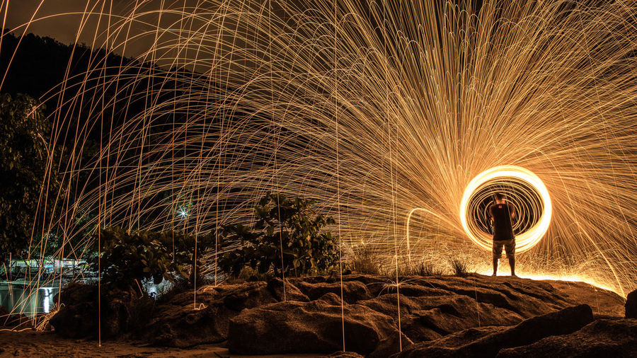 Rear view of man standing against wire wool