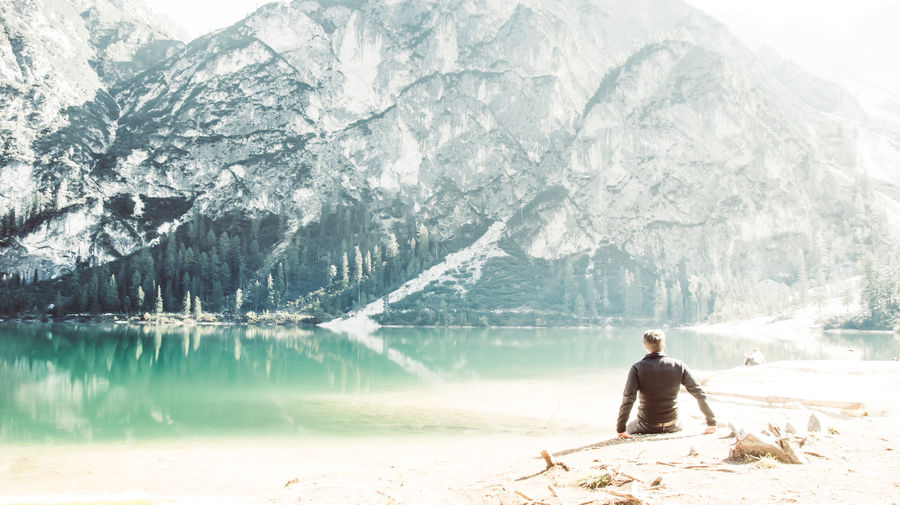 Rear view of man sitting at lakeshore against snowcapped mountains