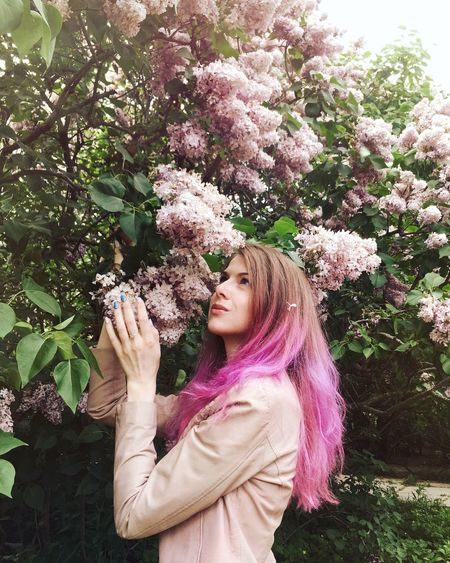 Young Woman Touching Pink Flowers Blooming On Tree