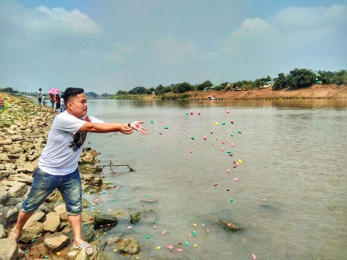 Man throwing food in lake
