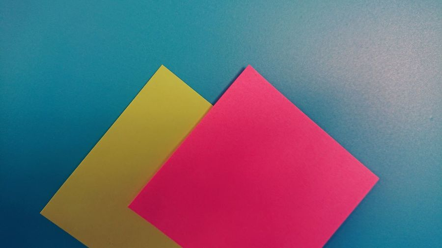 High angle view of multi colored paper against blue background