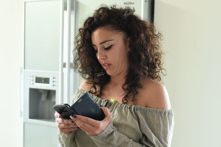 Mobile Phone Adult Casual Clothing Communication Connection Curly Hair Front View Hair Hairstyle Holding Indoors  Looking Looking Down Mobile Phone One Person Technology Telephone Using Mobile Phone Waist Up Wavy Hair Wireless Technology Women Young Adult