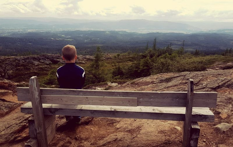Rear view of boy sitting on mountain against sky