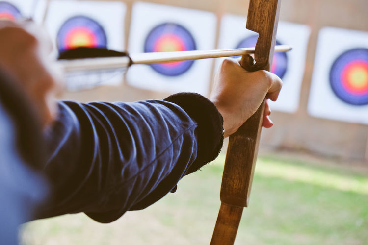 Archer holds his bow aiming at a target Arrow Bow Archer Archery Archery Bows Archery Competition Archery Target Close-up Human Hand Leisure Activity Lifestyles One Person People Skill  Sport Sports Photography Sports Target