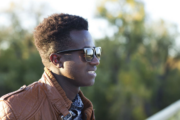 Handsome young black man with sunglasses and a leather jacket African American Autumn Leather Looking Away Profile Sunlight Young Black Confident  Fall Focus On Foreground Handsome Jacket Kenyan Milennial One Person Outdoors Selective Focus Smiling Sunglasses Sunlight ☀ Young Adult