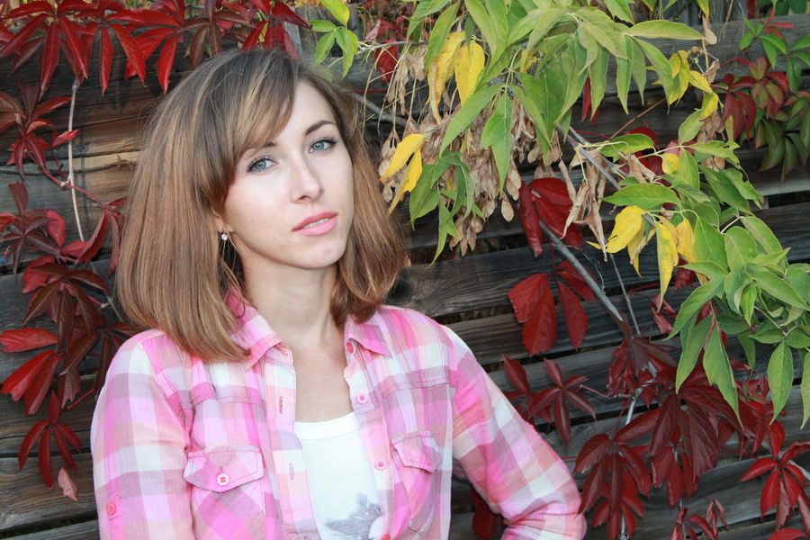 the girl in a garden, red leaves, autumn, informal hairstyle, the girl with green eyes in a pink shirt in a cage; casual photo