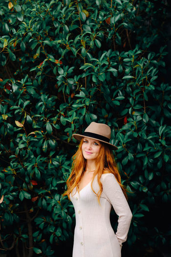 Portrait of woman standing by plants