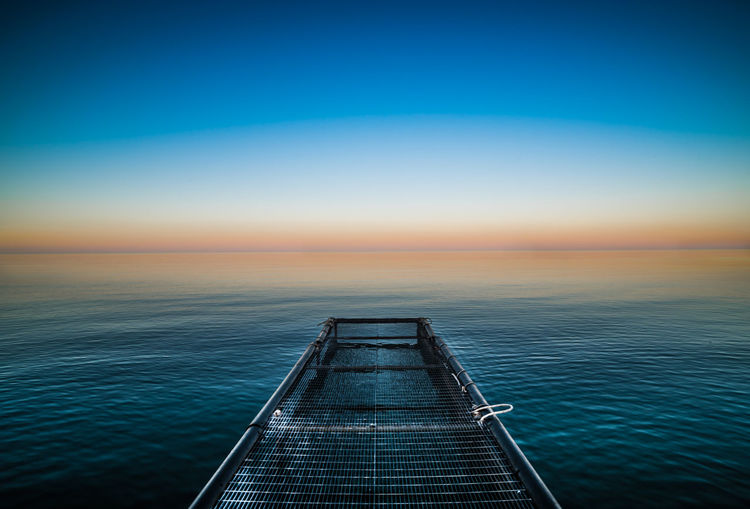 Metallic Jetty In Sea Against Sky During Sunrise
