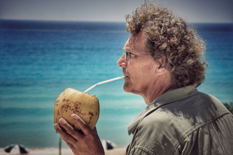 EyeEm Selects Coconut Sea Water Real People One Person Horizon Over Water Eyeglasses  Outdoors Beach Side View Coconut Drink Cocktail Day Leisure Activity Curly Hair Headshot Lifestyles Nature Sky Close-up People