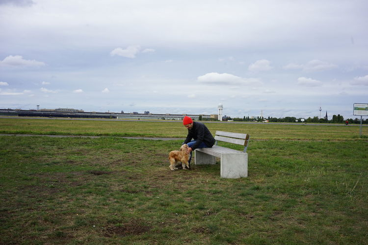 Man sitting with dog on field