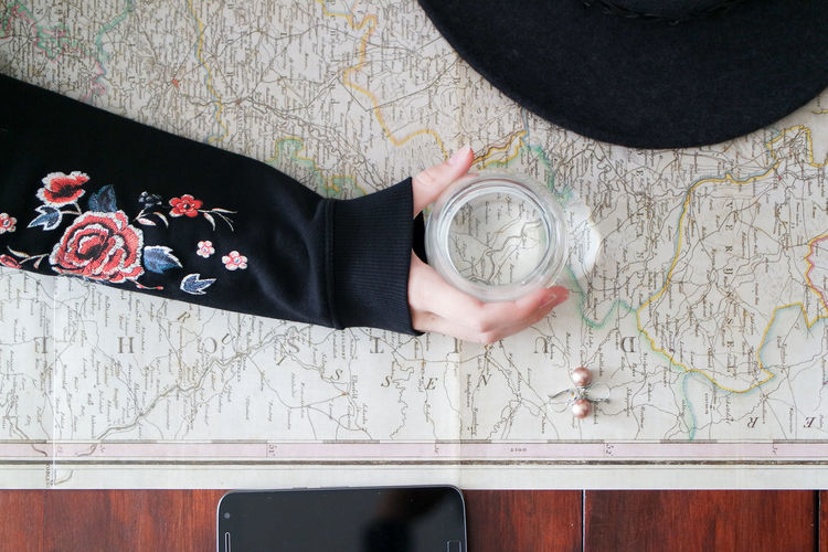 Directly above shot of woman using magnifying glass on map on table