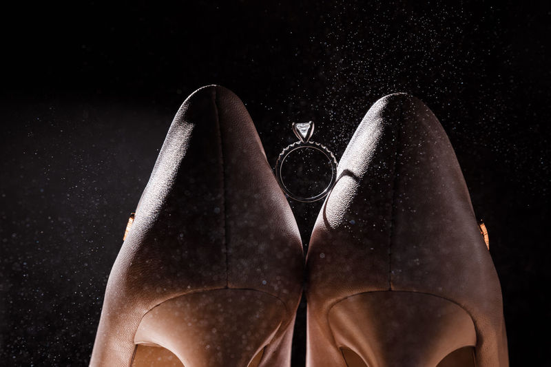 Low section of shoes against black background
