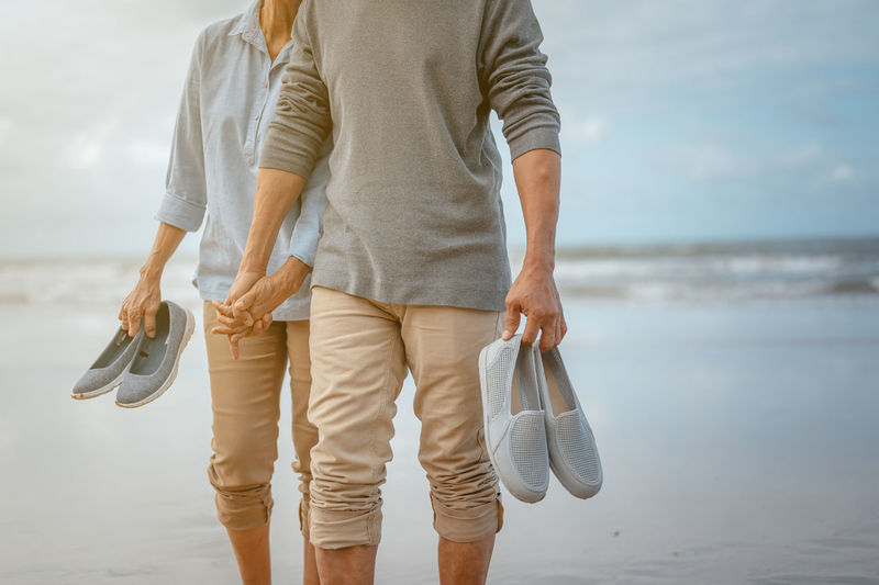 Midsection of couple holding footwears while walking on shore at beach