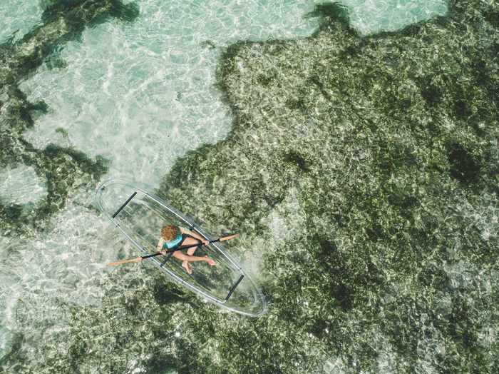 Aerial view of woman over inflatable boat in sea