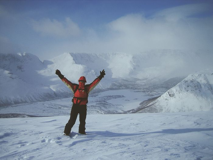 Man With Arms Raised Standing On Snowcapped Mountains