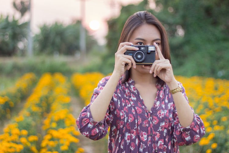 Young woman photographing with camera on field