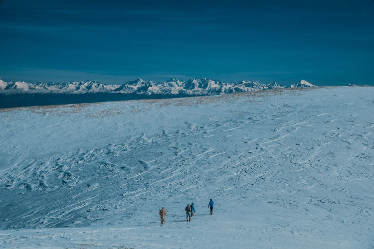 High angle view of people walking on snow covered land against sky