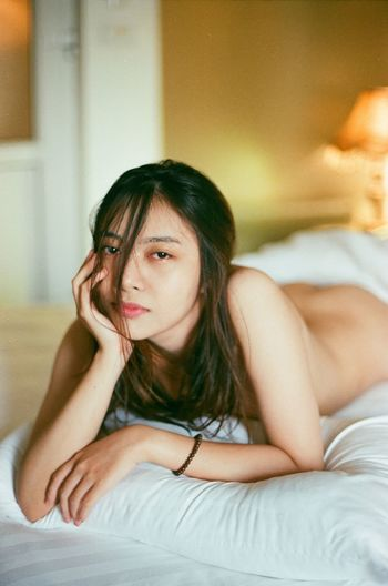 Portrait of naked woman on bed at home