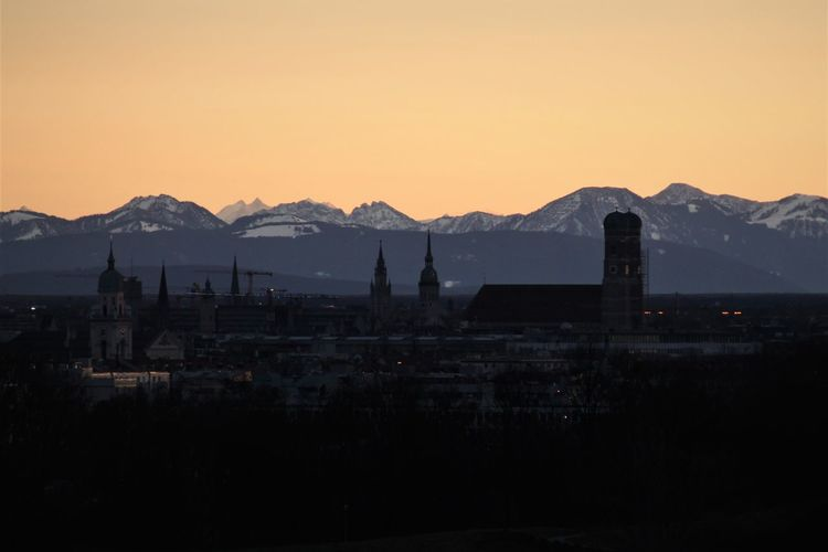 Silhouette buildings by mountains against clear sky during sunset