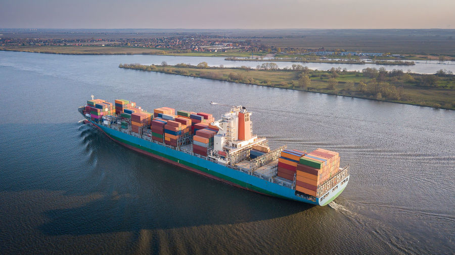 High angle view of container ship in sea against sky