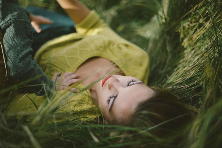 Midsection of woman resting on field