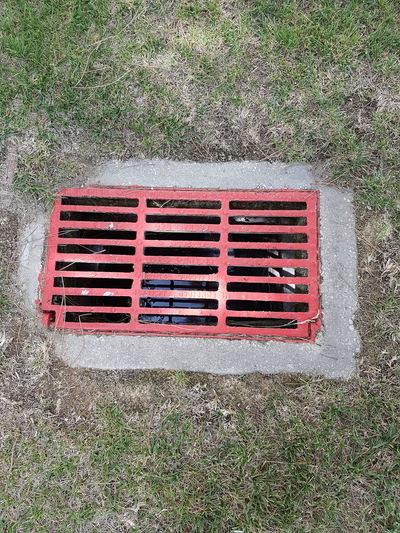 High angle view of red metal grate on grass
