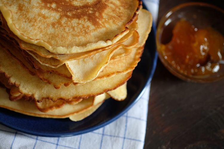 Stack of pancakes with maple syrup on table
