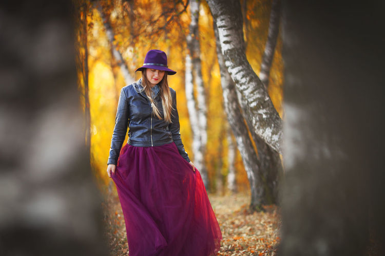 Woman wearing hat while standing in forest during autumn