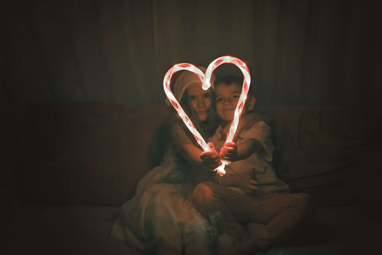 Siblings making heart shape of illuminated candy canes on sofa in darkroom