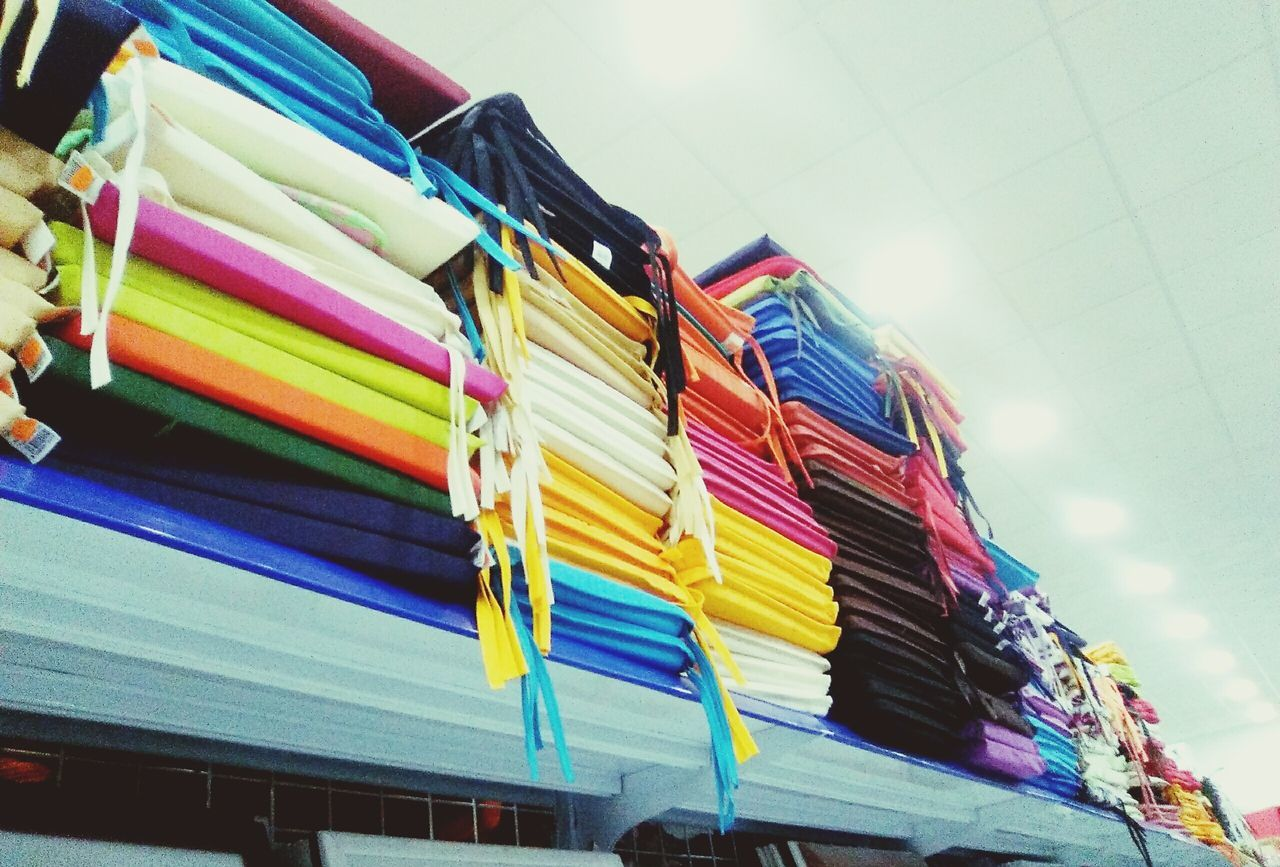 Stack Of Multi Colored Fabrics On Shelf For Sale In Shop