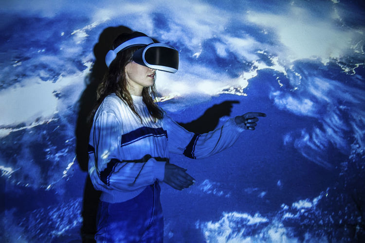 Close-up of woman wearing virtual reality standing against illuminated wall