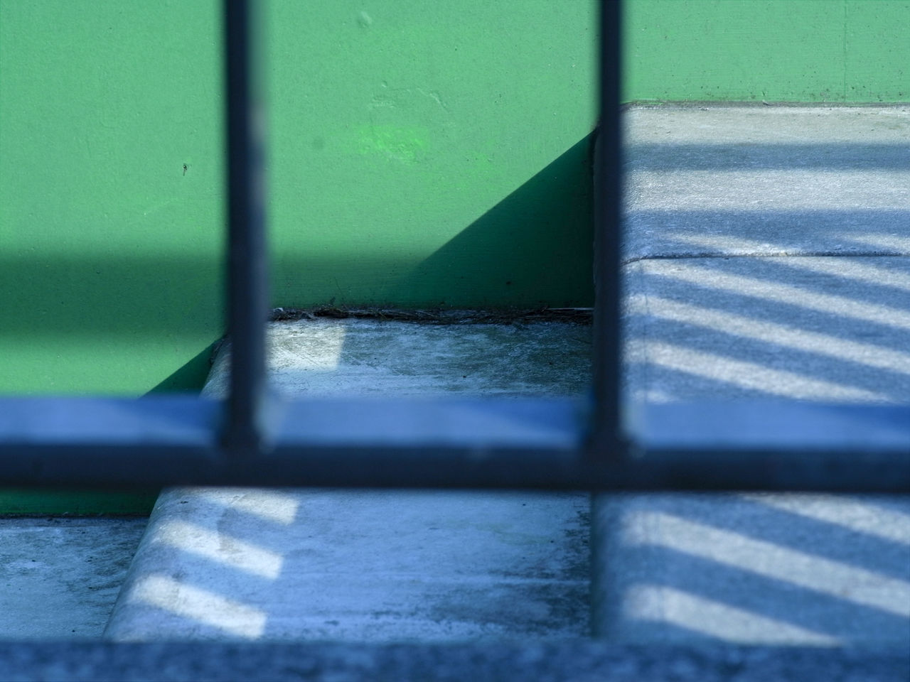 shadow, no people, day, green color, sunlight, nature, outdoors, wall - building feature, architecture, focus on background, built structure, footpath, grass, metal, absence, close-up, water, street, staircase