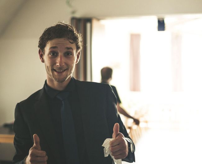 Portrait Of Smiling Businessman Gesturing Thumbs Up