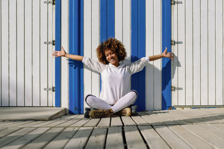 Young black woman on roller skates sitting near a beach hut. Girl with afro hairstyle rollerblading on sunny promenade. Happiness Happy Happy People Open Arms Curly Hair Day Exercising Flexibility Full Length Indoors  Leisure Activity Lifestyles One Person People Real People Rollerblading Rollerskating Sitting Skates Young Adult Young Women