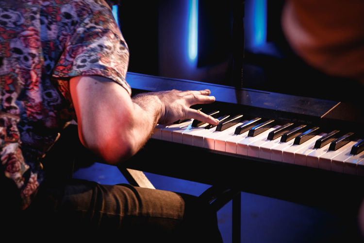 Midsection of man playing piano in recording studio