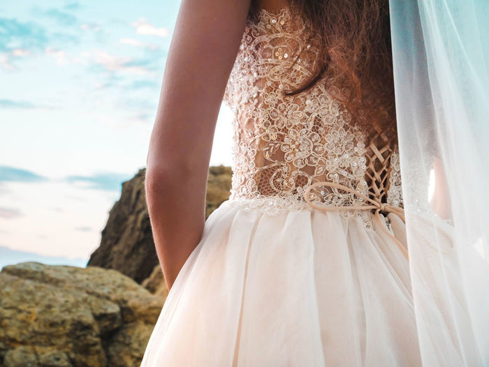 Unrecognizable girl in wedding luxury dress watching sunrise on sea shore. Bride on a rocks. Woman enjoying happy moments with nature. Adult Beautiful Woman Bride Celebration Clothing Day Dress Event Fashion Focus On Foreground Hairstyle Life Events Lifestyles Midsection Nature Newlywed One Person Outdoors Real People Rear View Sea Wedding Wedding Ceremony Wedding Dress Women