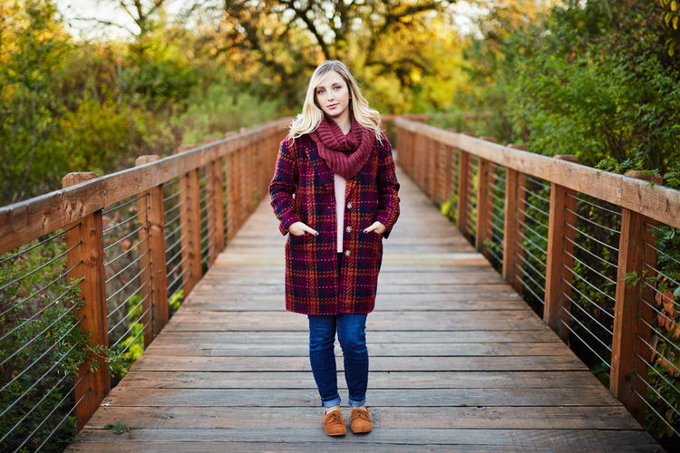 Autumn Beautiful People Beautiful Woman Beauty Beauty In Nature Bridge - Man Made Structure Cold Temperature Day Footbridge Front View Full Length Lifestyles Looking At Camera Nature One Person Outdoors Portrait Railing Real People Red Scarf Smiling Tree Walking Winter