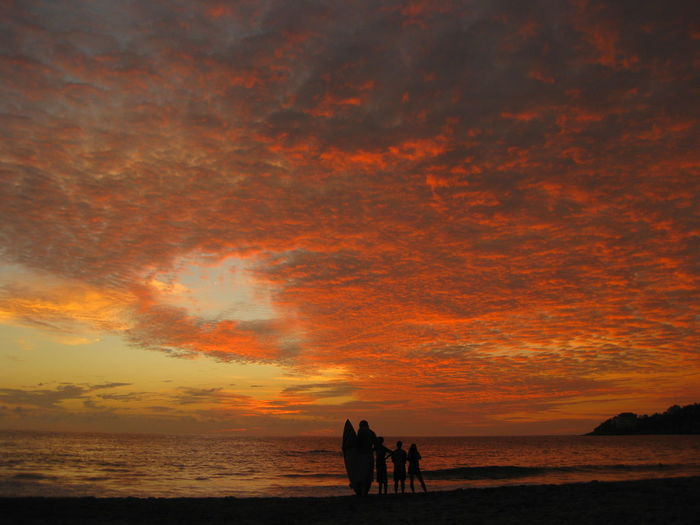 Silhouette of people on mexico beach against orange sky