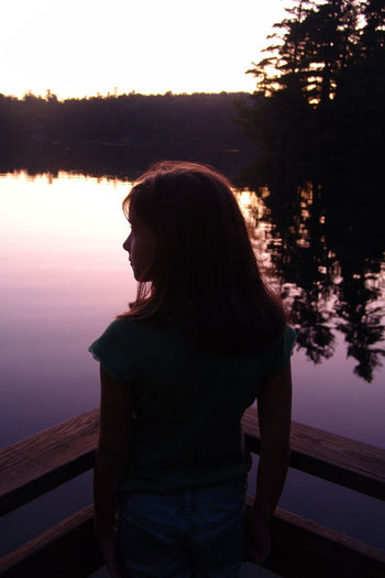 Portrait of young woman standing on lake during sunset