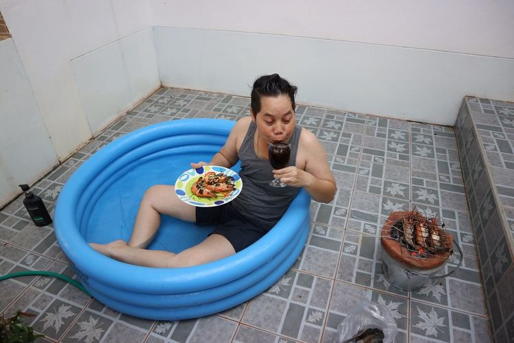 High angle view of woman having food while sitting in inflatable pool