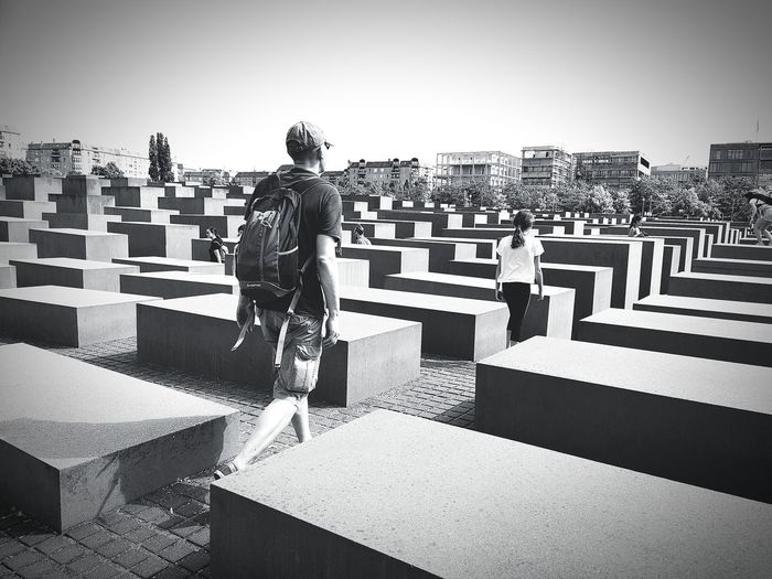 Rear view of man standing on cemetery against cityscape