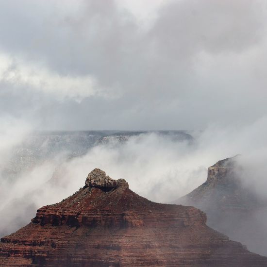 Scenic view of clouds over mountain against cloudy sky